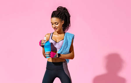 Resting time. Sporty girl with towel on shoulders drinks protein cocktail. Photo of african american girl with perfect body on pink background. Strength and motivation 스톡 콘텐츠
