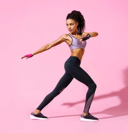 Warming up before training. Photo of sporty girl with perfect body on pink background. Strength and motivation 스톡 콘텐츠