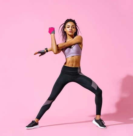 Warming up before training. Photo of sporty girl with perfect body on pink background. Strength and motivation Фото со стока