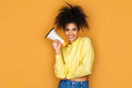 Smiling girl holds megaphone in hand. Photo of african american girl on yellow background Фото со стока
