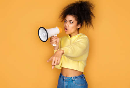 Girl shouts in megaphone and points forefinger to the side. Photo of african american girl on yellow background