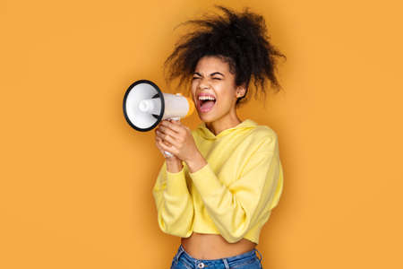 Girl shouts in megaphone. Photo of african american girl on yellow background