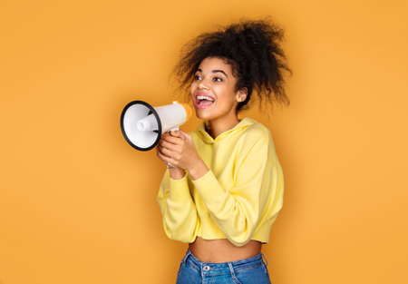 Happy girl shouts in megaphone. Photo of african american girl on yellow background