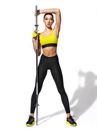 Sporty girl doing exercises with barbell. Photo of girl with perfect body on white background. Strength and motivation 스톡 콘텐츠