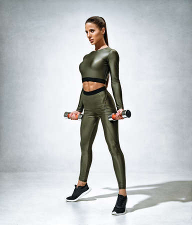 Sporty woman training with dumbbells. Photo of woman in sportswear on gray background. Strength and motivation. 스톡 콘텐츠