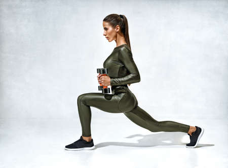 Sporty woman training with dumbbells. Photo of woman in sportswear on gray background. Strength and motivation. Side view