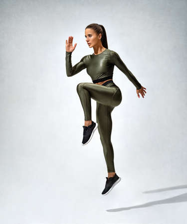 Sporty woman jumping. Photo of woman in sportswear on gray background. Strength and motivation. Dynamic movement