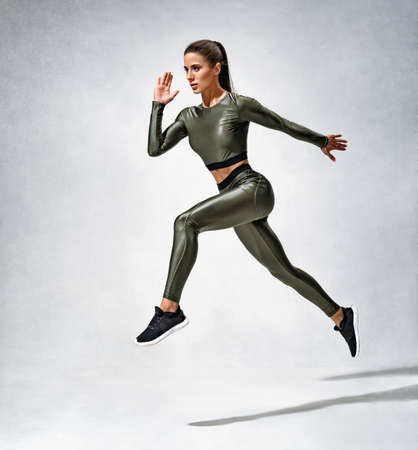 Sporty girl runner in silhouette. Photo of woman in sportswear on gray background. Strength and motivation.