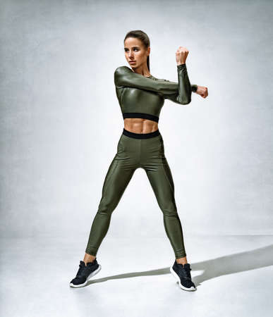 Spoty girl stretches her arms before training. Photo of woman in sportswear on gray background. Strength and motivation.