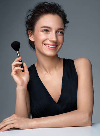 Woman with makeup brush for powder. Photo of woman with perfect makeup on gray background. Beauty concept