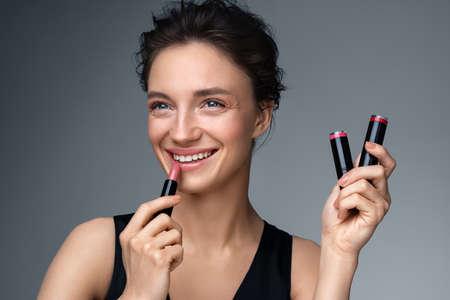 Woman applying lipstick. Photo of woman with perfect makeup on gray background. Beauty concept Фото со стока