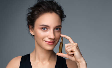 Woman holds ampoule with serum for hair or skin care. Photo of attractive woman with perfect makeup on gray background. Beauty concept