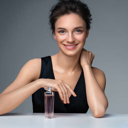Woman with bottle of perfume. Photo of woman with perfect makeup on gray background. Beauty concept