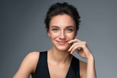 Beautiful woman with perfect makeup on gray background. Beauty and skin care concept 스톡 콘텐츠