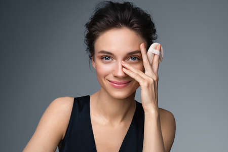Beautiful woman applying dry powder, using cosmetic cushion on her facial skin. Photo of woman with perfect makeup on gray background. Beauty concept