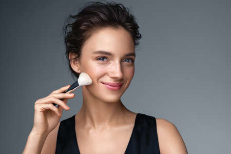 Woman applying rouge on the face using makeup brush. Photo of woman with perfect makeup on gray background. Beauty concept 스톡 콘텐츠