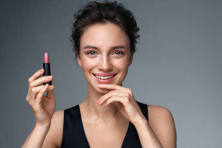 Woman applying lipstick. Photo of woman with perfect makeup on gray background. Beauty concept 스톡 콘텐츠