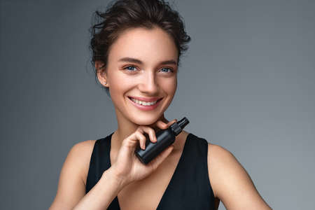 Woman with finishing spray. Photo of woman with perfect makeup on gray background. Beauty concept 스톡 콘텐츠
