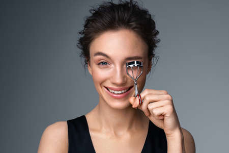 Beautiful woman using eyelash curler on long eyelashes. Photo of woman with perfect makeup on gray background. Beauty concept