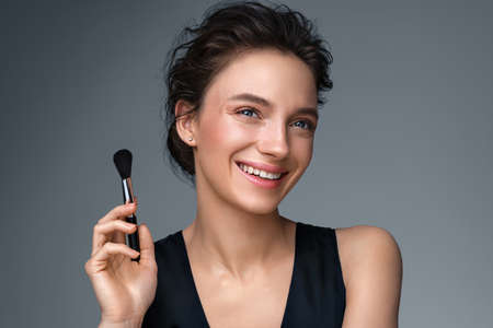 Woman with makeup brush. Photo of woman with perfect makeup on gray background. Beauty concept