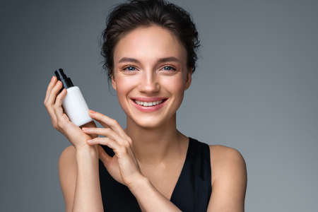 Woman holds bottle with cosmetic cream. Photo of attractive woman with perfect makeup on gray background. Beauty concept 스톡 콘텐츠