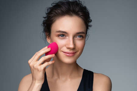 Woman applying foundation using cosmetic sponge, beauty blender. Photo of woman with perfect makeup on gray background. Beauty concept Фото со стока
