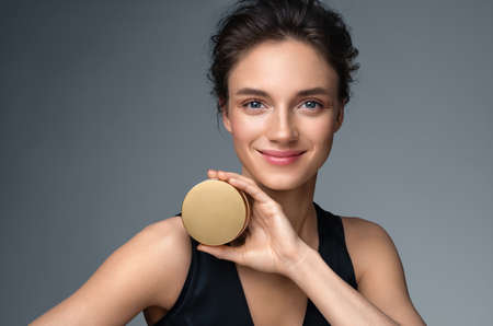 Woman holds jar with cosmetic cream. Photo of attractive woman with perfect makeup on gray background. Beauty concept