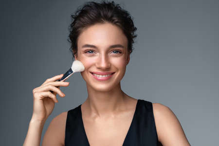 Woman applying rouge on the face using makeup brush. Photo of woman with perfect makeup on gray background. Beauty concept Фото со стока