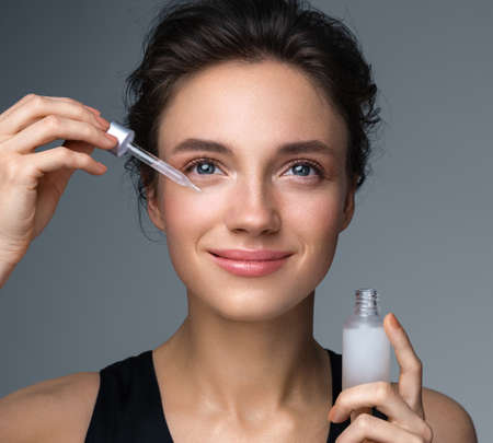 Woman applying hyaluronic serum on fer face with pipette. Photo of attractive woman with perfect makeup on gray background. Beauty concept Фото со стока