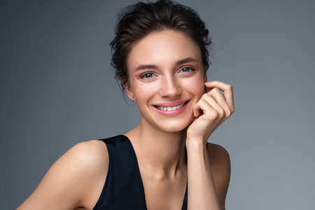 Beautiful woman with perfect makeup on gray background. Beauty and skin care concept 版權商用圖片