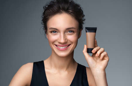 Woman with liquid foundation. Photo of woman with perfect makeup on gray background. Beauty concept