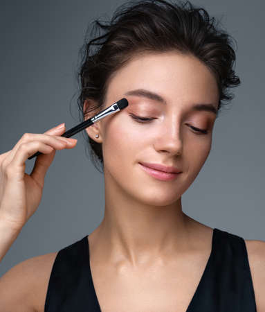 Beautiful woman using brush for eyeshadow. Photo of woman with perfect makeup on gray background. Beauty concept