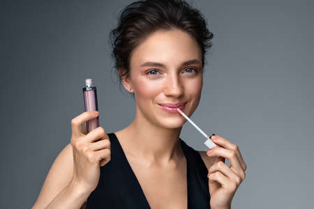 Woman with lip gloss. Photo of woman with perfect makeup on gray background. Beauty concept
