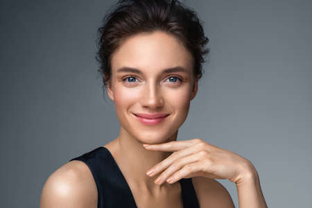 Beautiful woman with perfect makeup on gray background. Beauty and skin care concept Фото со стока
