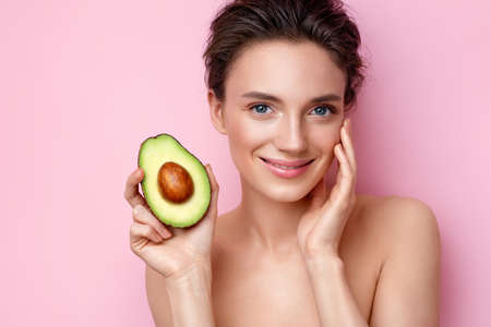 Smiling young woman with half an avocado. Photo of attractive woman with perfect makeup on pink background. Beauty & Skin care concept