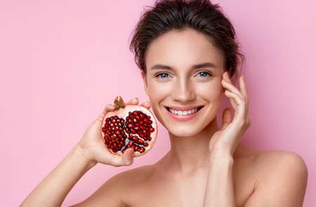 Laughing young woman with half an pomegranate. Photo of beautiful woman with perfect makeup on pink background. Beauty & Skin care concept