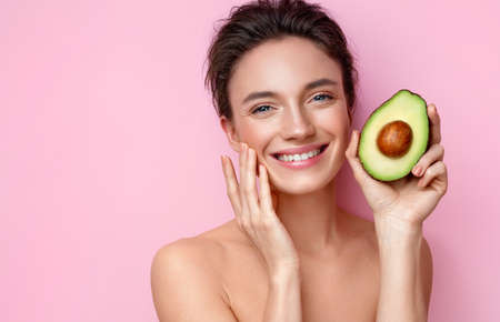 Laughing young woman with half an avocado. Photo of attractive woman with perfect makeup on pink background. Beauty & Skin care concept 版權商用圖片