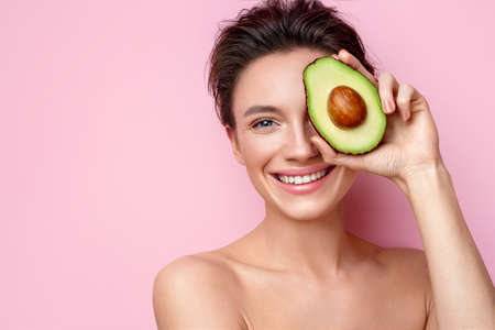 Pretty young woman holding half an avocado in front of her face. Photo of attractive woman with perfect makeup on pink background. Beauty & Skin care concept