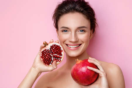 Laughing young woman with pomegranates. Photo of attractive woman with perfect makeup on pink background. Beauty & Skin care concept