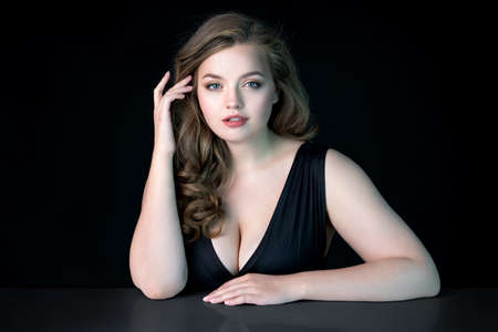Young beautiful woman with natural makeup on black background. Beauty & Skin care concept. Plus size model.