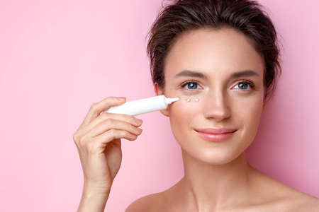 Beautiful woman using cream around the eyes. Photo of woman with perfect makeup on pink background. Beauty and skin care concept 版權商用圖片