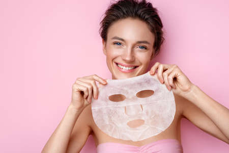 Smiling young woman holds cosmetic facial mask. Photo of attractive woman with perfect makeup on pink background. Beauty & Skin care concept