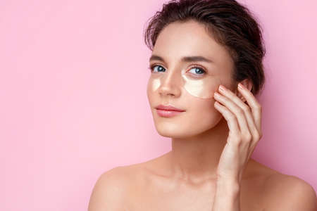 Woman with eye patches touching hand her face. Photo of attractive woman on pink background. Beauty and skin care concept