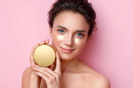 Woman with eye patches showing jar with cosmetic cream. Photo of beautiful woman on pink background. Beauty and skin care concept