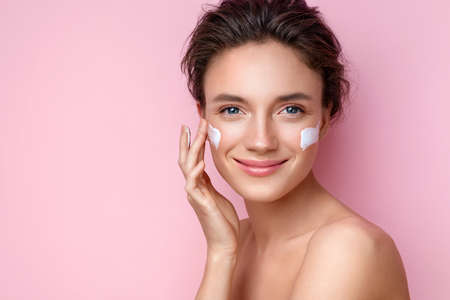 Beautiful woman applying moisturizer cream on her face. Photo of smiling woman with perfect makeup on pink background. Beauty concept 版權商用圖片