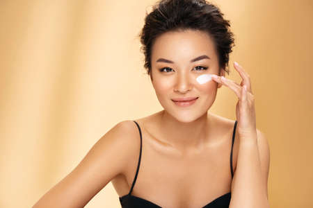 Beautiful woman applying moisturizer cream on her face. Photo of asian woman with perfect makeup on beige background. Beauty concept