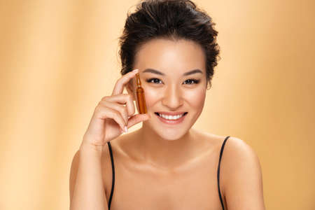 Woman holds ampoule with serum for hair or skin care. Photo of attractive asian woman with perfect makeup on beige background. Beauty concept 版權商用圖片