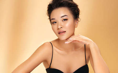 Beautiful woman with perfect makeup on beige background. Beauty and skin care concept