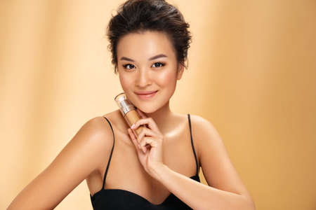 Woman with liquid foundation. Photo of asian woman with perfect makeup on beige background. Beauty concept