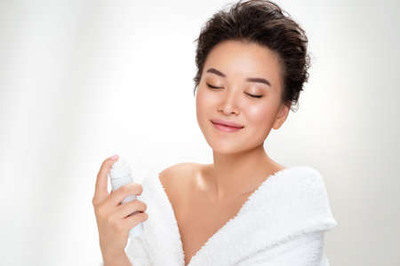 Beautiful woman using spray with thermal water. Photo of asian woman after shower on white background. Beauty and skin care concept
